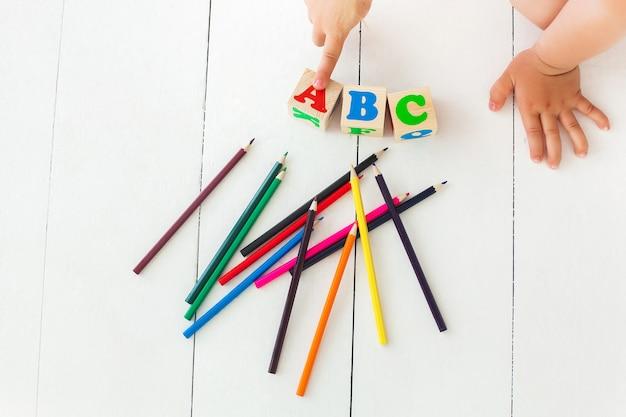 小さな子供がabcキューブを指しています。アルファベットの背景。中立的な背景にabcレンガ。カラフルな鉛筆 Premium写真