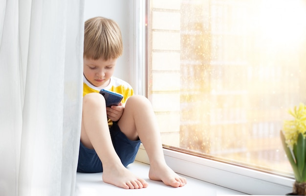 Little child with smartphone on windowsill, space for text. concept - quarantine, danger of internet. Premium Photo