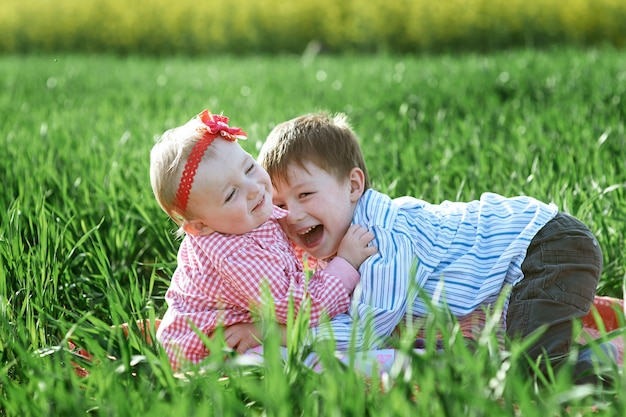 Little children boy and girl play on green grass Premium Photo