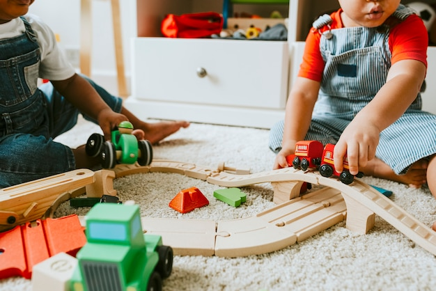 Little children playing with a railroad train toy Premium Photo