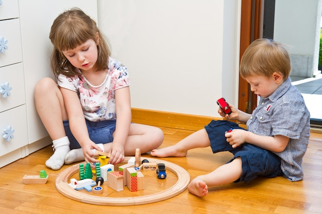 Little children playing with wooden train in the room Premium Photo
