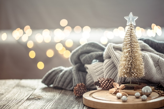 Little christmas tree over christmas lights bokeh in home on wooden table with sweater on a wall and decorations. Free Photo