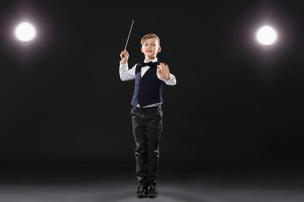 Маленький дирижер на темной сцене Premium Фотографии