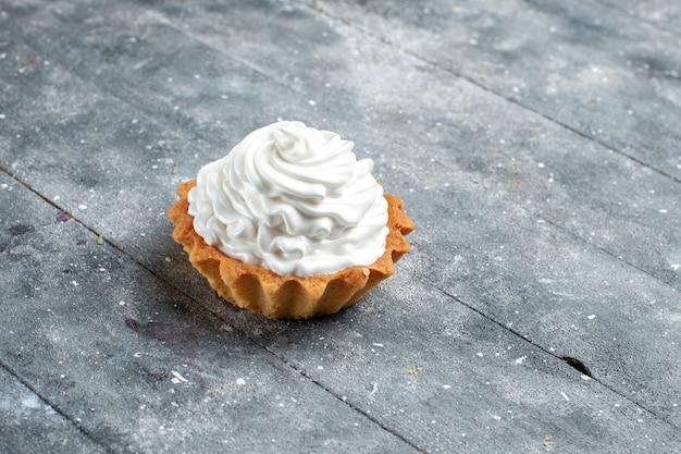 灰色の机の上に隔離されたおいしい焼きたての小さなクリーミーなケーキ、ケーキビスケット甘い砂糖クリーム 無料写真
