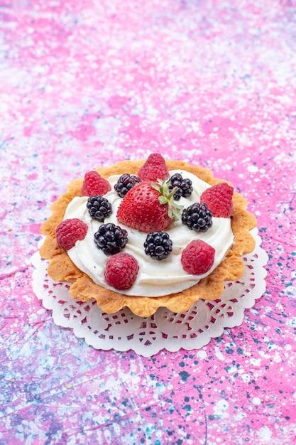 光の上のベリーと小さなクリーミーなケーキ、ケーキビスケットベリーの甘い焼き写真 無料写真