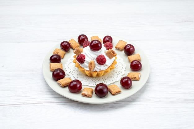 Сливочный торт с малиной и маленьким печеньем на белом свете Бесплатные Фотографии
