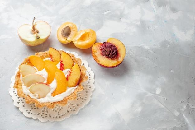 Маленький сливочный торт с нарезанными фруктами и белым кремом вместе со свежими абрикосами и персиками на столе с белым светом, фруктовый торт, печенье, печенье Бесплатные Фотографии