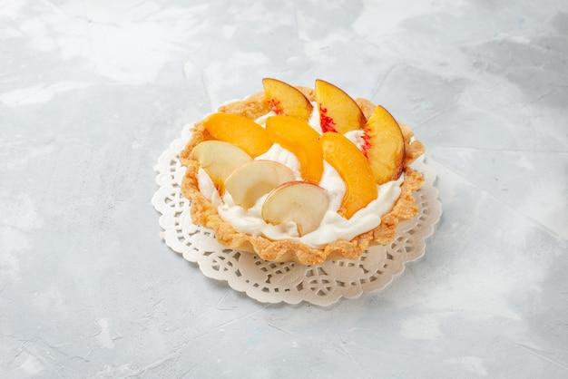 ホワイトライトデスクにスライスしたフルーツと白いクリームが入った小さなクリーミーなケーキ、フルーツケーキの甘いビスケットクッキーの味 無料写真