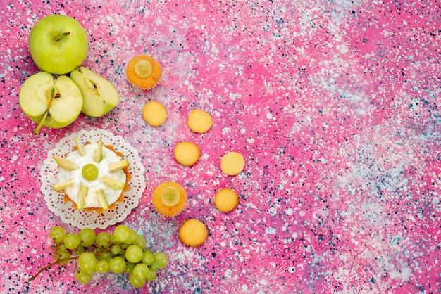 色付きの机の上にスライスしたフルーツクッキーブドウと小さなクリーミーなケーキ、ケーキ甘い砂糖焼き色 無料写真