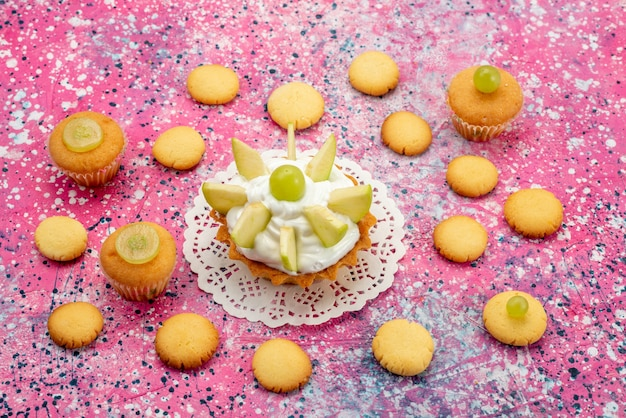 色付きの机の上にスライスしたフルーツクッキー、ケーキシュガーと小さなクリーミーなケーキ 無料写真