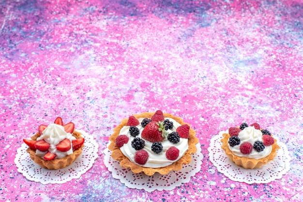 Кремовые лепешки с разными ягодами на светло-белом, пирожное ягодное сладкое Бесплатные Фотографии