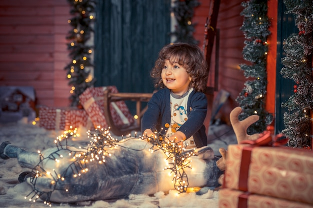 A little curly sweet kid boy in jeans playing with deer toy and christmas lights in the living room on christmas Premium Photo