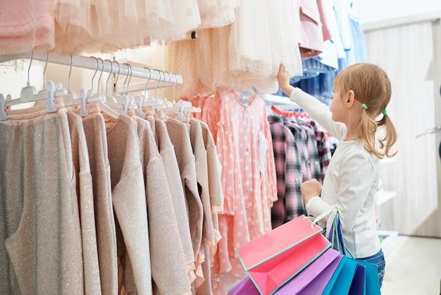 작은 고객 상점에 서서 새 드레스를 선택 무료 사진