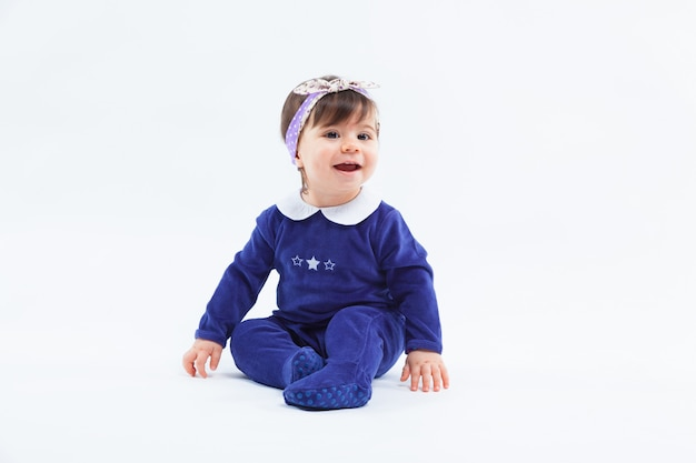 Little cute adorable smiling girl with bow in hair sitting posing on white Premium Photo