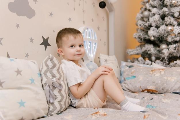 크리스마스 트리 옆에 풍선 모양의 야간 조명과 나무 침대 집에서 어린이 방에 앉아 작은 귀여운 아기 프리미엄 사진