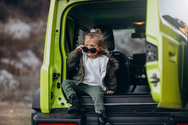 Little cute baby girl sitting in the back of the car Free Photo