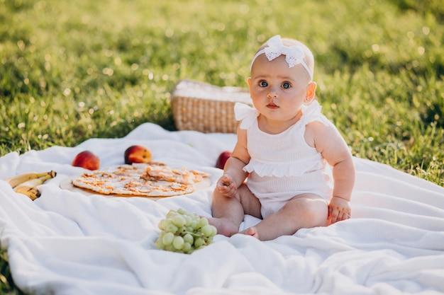 Маленькая милая девочка сидит на одеяле в парке Бесплатные Фотографии