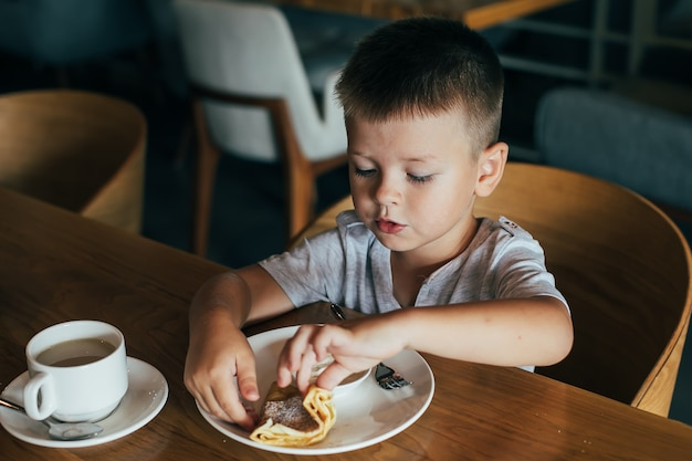 Little and cute boy having breakfast in cafe. Premium Photo
