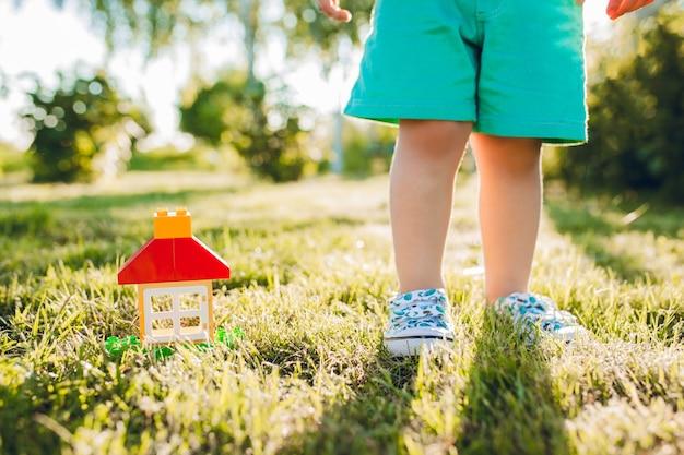 Piccolo ragazzo carino e la sua casa nel giardino estivo. Foto Gratuite