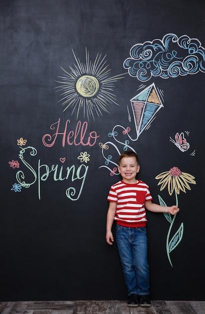 Little cute boy holding flower on the chalk black board Free Photo