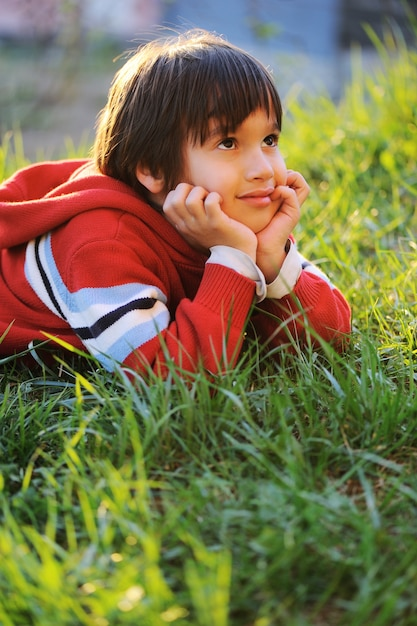 little cute boy laying on morning summer grass with natural