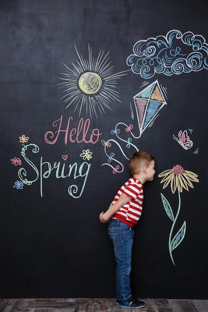 Little cute boy smelling flower on the chalk black board Free Photo