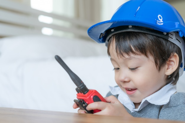 Little cute boy wearing blue helmet and enjoying to talking with red walkie-talkie redio in the bedroom Free Photo