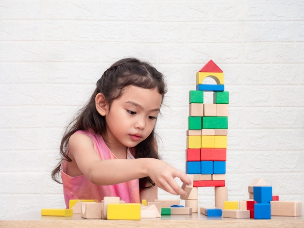 Little cute girl 6 years old playing wooden blocks on table and white bricks wall Premium Photo