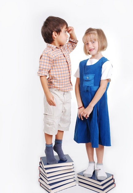 Little Cute Girl And Boy With Many Books Isolated Photo Premium