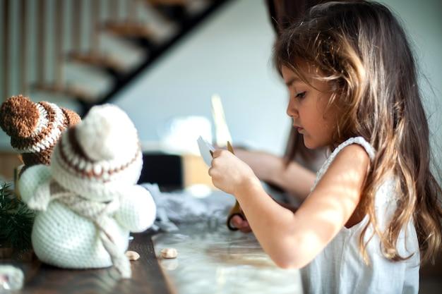 かわいい女の子と若い美しい女性は白い紙から雪片を切り取りました。ジンジャーブレッドとマシュマロ入りココア。新年とクリスマスの準備の概念。 Premium写真