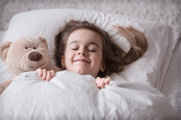 Little cute girl in bed with toy Free Photo