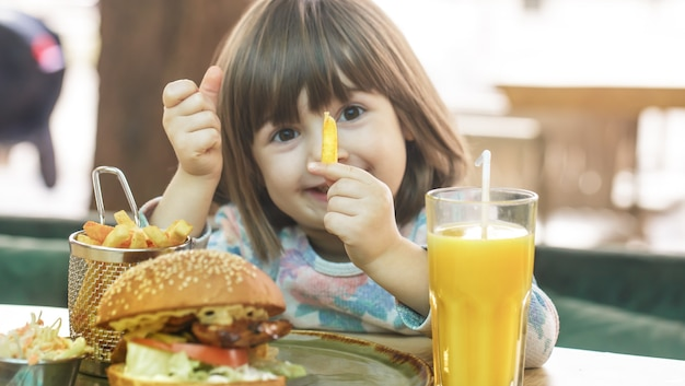 カフェでフライドポテトとオレンジジュースのファーストフードサンドイッチを食べるかわいい女の子。ファーストフードのコンセプト。 無料写真