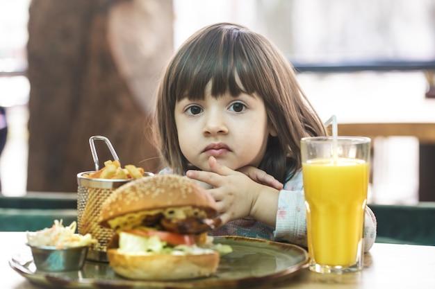 카페에서 감자 튀김과 오렌지 주스와 패스트 푸드 샌드위치를 먹는 귀여운 소녀. 패스트 푸드 개념. 무료 사진