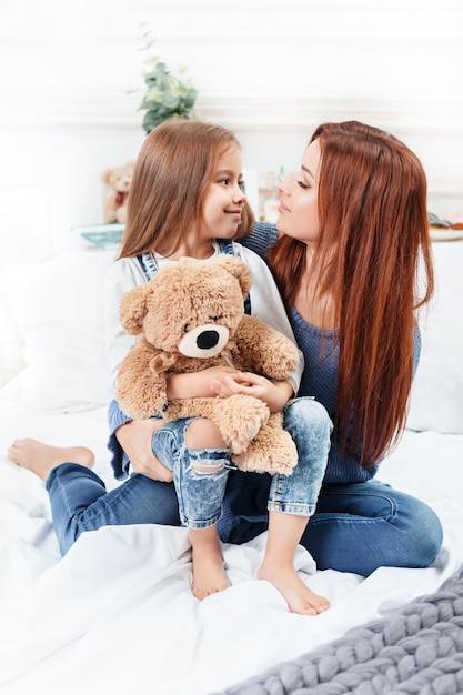 Bambina carina godendo, giocando e creando con il giocattolo con la madre Foto Gratuite