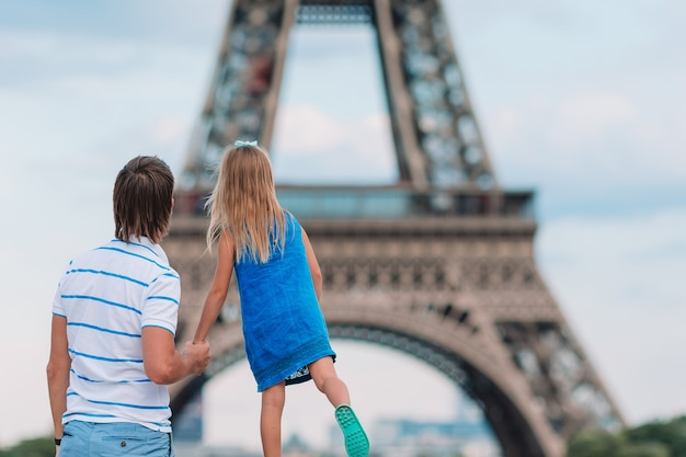 Little cute girl and her father in paris near eiffel tower during summer french vacation Premium Photo