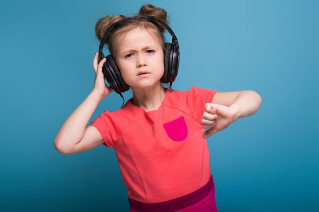 Little cute girl in pink dress and headphones Premium Photo