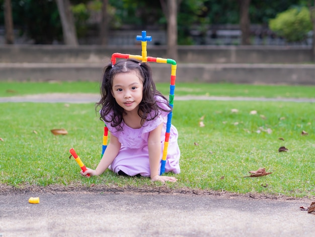 Little cute girl play the pipe toy,connected to the gate and entrance. Premium Photo
