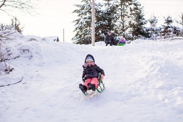 Little cute girl pulls a sled in warm winter day Premium Photo