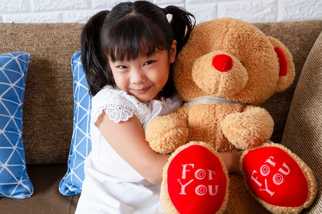 Little cute girl showing big teddy bear with happiness Free Photo