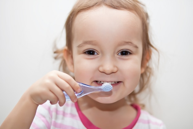 Маленькая милая девушка smailing и чистить зубы. Premium Фотографии