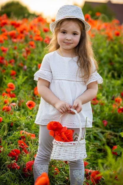 Маленькая милая девочка с корзиной с букетом маков стоит в поле маков, чешский репаблик Premium Фотографии