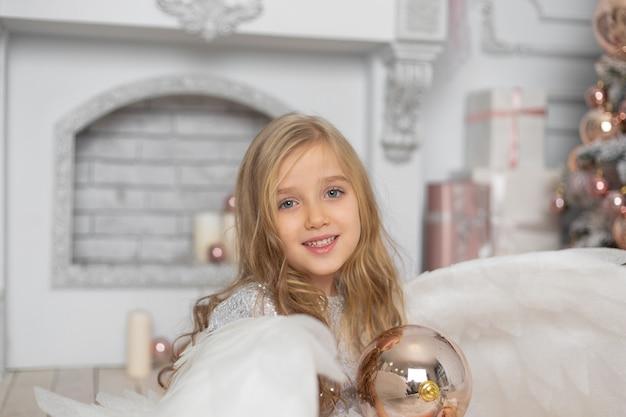 クリスマスツリーの隣のスタジオで天使の羽を持つブロンドの髪の少女 Premium写真