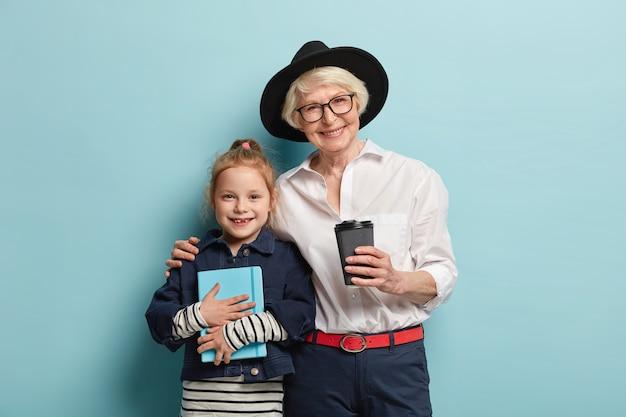 メモ帳を持ったかわいい女の子は、おばあちゃんと一緒に自由な時間を過ごし、気分が良く、持ち帰り用のコーヒーを飲み、抱きしめます。笑顔の年配の先生は小さな子供の生徒を抱きしめ、屋内で一緒に勉強します 無料写真