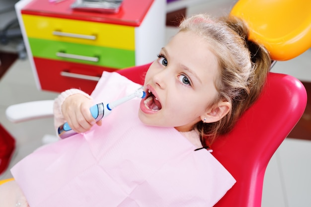 Little cute girl without front milk teeth in red dental chair with electric automatic toothbrush in hands. Premium Photo