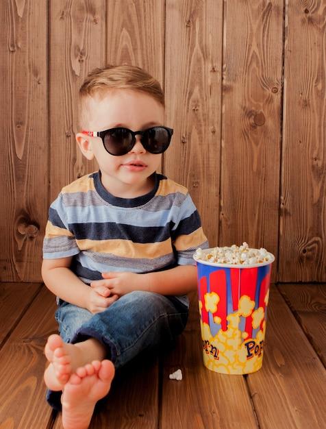 小さなかわいい子供男の子2〜3歳、ポップコーンのバケツを保持し、木製の背景にファーストフードを食べる3dimaxシネマメガネ。子供の子供時代のライフスタイルのコンセプト。スペースをコピーします。 Premium写真