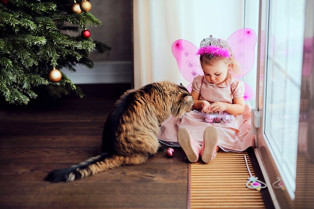Little cute kid in fairy costume playing with cat near christmas tree Premium Photo