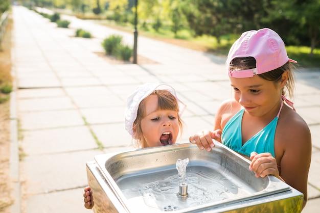 작은 귀여운 목 마른 소녀는 화창한 더운 여름 날에 거리에 마시는 싱크대에서 물을 마신다 프리미엄 사진