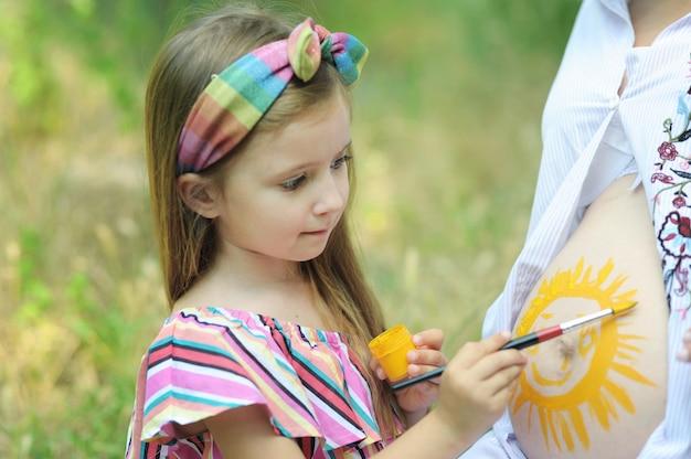 Маленькая дочка рисует солнышко на животе беременной матери Premium Фотографии