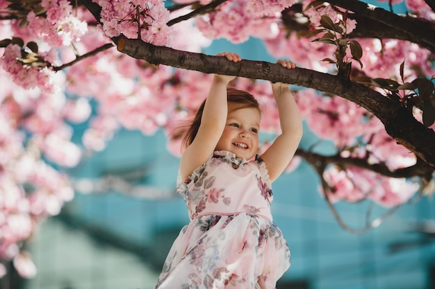 Little daughter holds a branch of blooming pink tree Free Photo