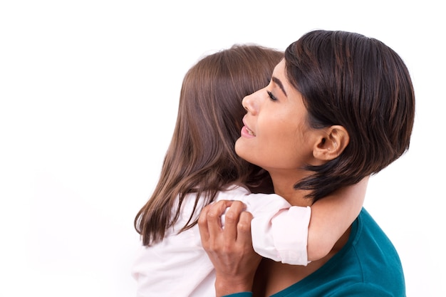 Little daughter hugging her mother, concept of happy family or love Premium Photo